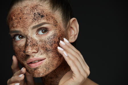 Beauty Face Care. Portrait Of Attractive Young Woman Putting Coffee Scrub On Facial Skin. Closeup Beautiful Sexy Female Model Touching Face With Hands, Exfoliating And Scrubbing Skin. High Resolution Imagens