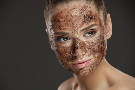 Face Care. Closeup Of Young Woman With Natural Makeup And Coffee Scrub Mask On Fresh Facial Skin. Portrait Of Beautiful Sexy Female Model With Peeling Cosmetic Product On Beauty Face. High Resolution Stock Photo