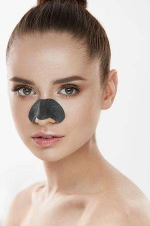 Cosmetology. Portrait Of Beautiful Female Model With Black Mask On Nose. Closeup Of Healthy Young Woman With Pure Soft Skin And Fresh Natural Makeup. Beauty And Skin Care Treatment. High Resolution