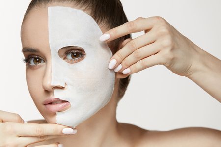 Female Beauty Face Skin Treatment. Closeup Beautiful Sexy Young Woman With Natural Makeup, White Cosmetic Sheet Mask On Fresh Soft Facial Skin. Attractive Girl Applying Mask On Face. High Resolution