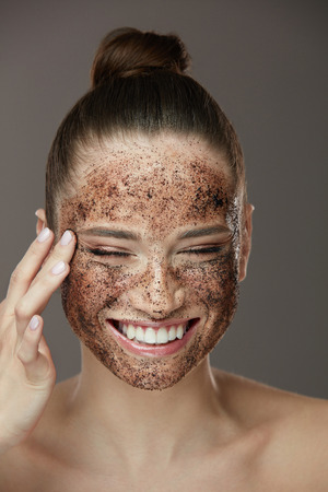 Face Skin Scrub. Portrait Of Sexy Smiling Female Model Applying Natural Coffee Mask, Face Scrub On Facial Skin. Closeup Of Beautiful Happy Woman With Face Covered With Beauty Product. High Resolution