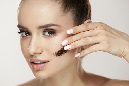 美容トリートメント。顔の皮膚にコーヒー スクラブを適用する若い女性の肖像画。新鮮な化粧と顔に化粧品のマスクのストライプとセクシーな美少