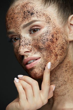 Face Care. Closeup Of Beautiful Woman With Natural Makeup And Skin Exfoliating Coffee Scrub On Beauty Face. Attractive Young Female Applying Mask, Doing Skin Peeling Spa Procedure. High Resolution Фото со стока - 78817436