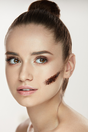 Beauty Cosmetics. Closeup Of Healthy Young Woman With Stripe Of Coffee Scrub Mask On Facial Skin. Portrait Of Beautiful Female With Pure Soft Skin And Fresh Makeup. Face Skin Care. High Resolution Фото со стока