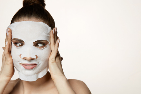 Skin Treatment. Portrait Of Attractive Young Woman Putting White Cosmetic Mask On Facial Skin. Closeup Of Beautiful Sexy Female Touching Face And Grimacing On White Background. High Resolution