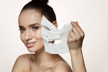 Gesicht Hautpflege. Portrait des schönen lächelnden Mädchens, das weiße Blatt-Maske von der gesunden frischen Haut entfernt. Nahaufnahme der attraktiven sexy Frau mit natürlichen Make-up und Maske auf Gesichts-Haut. Hohe Auflösung Standard-Bild - 78817511