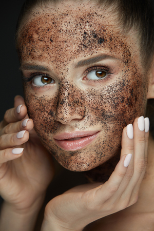 Beauty Face Care. Portrait Of Attractive Young Woman Putting Coffee Scrub On Facial Skin. Closeup Beautiful Sexy Female Model Touching Face With Hands, Exfoliating And Scrubbing Skin. High Resolution Фото со стока - 78817514