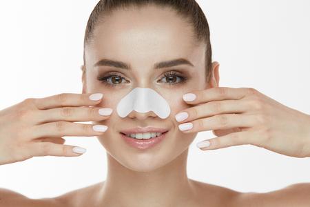 スキンケア。白いパッチと美しい女性美の顔のクローズ アップは毛穴鼻の帯です。きれいな柔らかい手と純粋な顔の皮膚に触れる新鮮なメイクとセ 写真素材