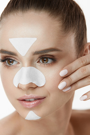 Beauty Cosmetics. Young Female With Cleansing Patches On Skin Touching Face. Closeup Of Attractive Girl With Fresh Natural Makeup And Facial Mask Strips On Nose, Chin And Forehead. High Resolution