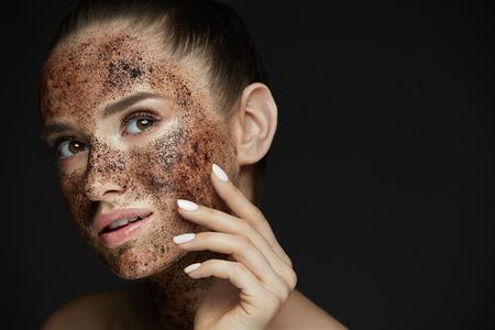 얼굴 관리. 자연스러운 메이크업 및 피부 미용 얼굴에 커피 스크럽 엑스 폴리 에이 팅 아름 다운 여자의 근접 촬영. 매력적인 젊은 여자 적용 마스크,