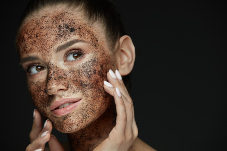 Beauty Face Care. Portrait Of Attractive Young Woman Putting Coffee Scrub On Facial Skin. Closeup Beautiful Sexy Female Model Touching Face With Hands, Exfoliating And Scrubbing Skin. High Resolution 스톡 콘텐츠