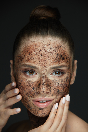 Beauty Face Care. Portrait Of Attractive Young Woman Putting Coffee Scrub On Facial Skin. Closeup Beautiful Sexy Female Model Touching Face With Hands, Exfoliating And Scrubbing Skin. High Resolution Stock Photo