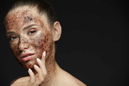 Face Care. Closeup Of Beautiful Woman With Natural Makeup And Skin Exfoliating Coffee Scrub On Beauty Face. Attractive Young Female Applying Mask, Doing Skin Peeling Spa Procedure. High Resolution Фото со стока - 78817550