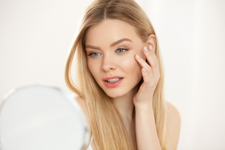 fresh face: Makeup And Beauty Care. Closeup Beautiful Sexy Woman With Fresh Natural Makeup And Healthy Soft Smooth Skin Touching Face And Looking In Mirror. Young Female Massaging Skin Under Eyes. High Resolution