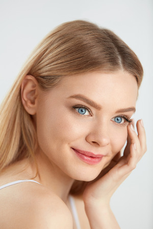 beautiful model: Woman Beauty Face Skin. Closeup Of Beautiful Young Female Model With Healthy Soft Smooth Skin And Fresh Natural Makeup. Portrait Of Attractive Smiling Girl Touching Face. Facial Care. High Resolution Stock Photo
