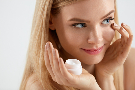 Beautiful Woman Face Skin Care. Portrait Of Young Female Applying Cream On Skin Under Eyes. Closeup Of Attractive Girl With Natural Makeup On Face Touching Facial Skin. Beauty Concept. High Resolution