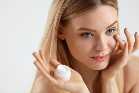 美人顔のスキンケア。眼の下の皮膚に若い女性を適用するクリームの肖像画。顔の皮膚に触れる顔に自然なメイクと魅力的な女の子のクローズ アッ