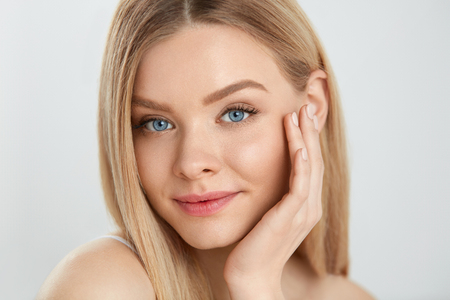 Woman Beauty Face Skin. Closeup Of Beautiful Young Female Model With Healthy Soft Smooth Skin And Fresh Natural Makeup. Portrait Of Attractive Smiling Girl Touching Face. Facial Care. High Resolution Stockfoto