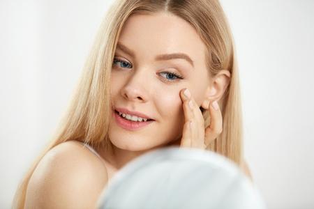 Make-up en schoonheidszorg. Close-up Mooie Sexy Vrouw Met Verse Natuurlijke Make-up En Gezonde Zachte Gladde Huid Aanraken Gezicht En In Spiegel kijken. Jonge vrouwelijke massage huid onder de ogen. Hoge resolutie