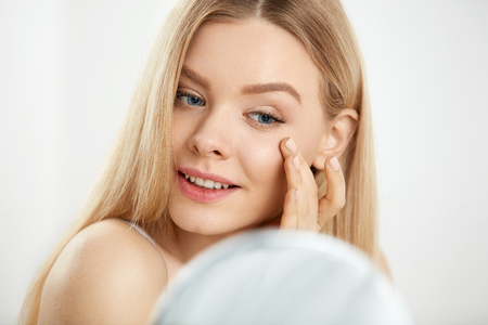 Maquillaje y cuidado de la belleza. Mujer hermosa hermosa del primer con maquillaje natural fresco y cara conmovedora suave sana de la piel y que mira en espejo. Joven mujer masajeando la piel debajo de los ojos. Alta resolución
