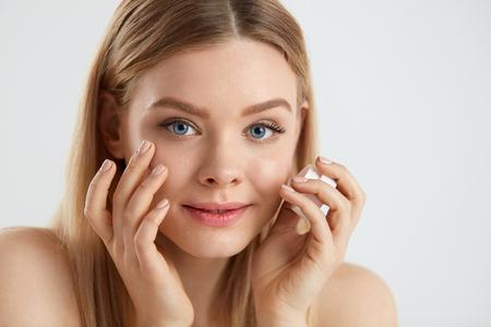 女顔のスキンケア。目の前でクリームを適用して、ボトルを保持している魅力的なの若い女性の肖像画。クローズ アップ自然化粧品と新鮮な肌を持