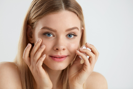 Woman Face Skin Care. Portrait Of Attractive Young Female Applying Cream Under Eyes And Holding Bottle. Closeup Of Smiling Girl With Natural Makeup And Fresh Skin. Beauty Cosmetics. High Resolution Reklamní fotografie