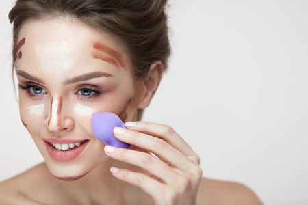 Face Makeup And Beauty Cosmetics. Portrait Of Beautiful Young Woman Applying Contour And Highlight Makeup Lines With Sponge Blender. Closeup Of Sexy Young Female Doing Facial Makeup. High Resolution Reklamní fotografie - 79355390