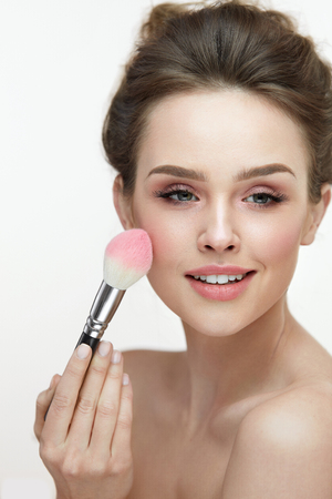 Woman Beauty Make-Up. Closeup Of Smiling Girl Applying Blush On Smooth Soft Skin. Portrait Of Beautiful Happy Female With Fresh Makeup Posing On White Background. Facial Cosmetics. High Resolution