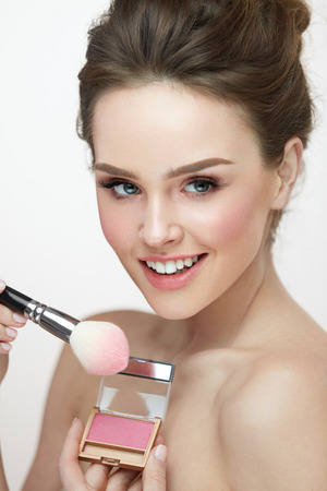 Beauty Cosmetics. Closeup Of Beautician Hands With Brush And Blush Box Applying Blusher On Smiling Womans Face. Portrait Of Beautiful Girl Getting Fresh Natural Makeup On Facial Skin. High Resolution Stock Photo