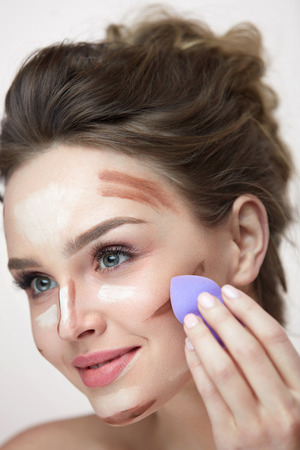 Face Makeup And Beauty Cosmetics. Portrait Of Beautiful Young Woman Applying Contour And Highlight Makeup Lines With Sponge Blender. Closeup Of Sexy Young Female Doing Facial Makeup. High Resolution