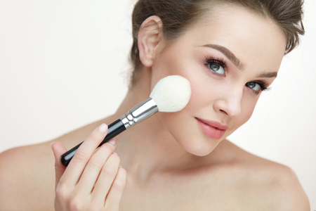 fresh face: Face Makeup Cosmetics. Portrait Of Sexy Young Woman With Clean Skin And Fresh Makeup. Closeup Beautiful Girl Holding Cosmetic Brush And Applying Blush On Facial Skin. Beauty Concept. High Resolution