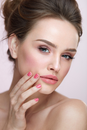 Beauty Makeup Cosmetics. Closeup Of Beautiful Woman Touching Soft Smooth Facial Skin. Portrait Of Sexy Young Female Model With Professional Natural Make-up, Pink Nails And Sexy Lips. High Resolution Stock Photo