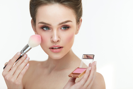 Woman Face Makeup. Portrait Of Female Getting Natural Fresh Facial Make-Up. Closeup Beautician Hands With Compact Blush And Brush Applying Blusher On Sexy Girl Face. Beauty Cosmetics. High Resolution