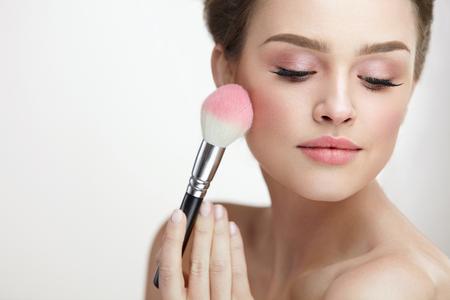 얼굴 미용 화장품. 얼굴에 핑크 느슨한 얼굴을 적용하는 순수한 부드러운 피부와 매력적인 여성의 초상화. 화장 용 브러시를 들고 신선한 메이크업으 스톡 콘텐츠