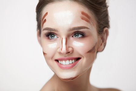Woman Beauty Makeup. Closeup Of Smiling Young Female Model With Contouring And Highlighting Face Lines On Skin. Portrait Of Beautiful Smiling Girl With Cosmetic Makeup Product On Skin. High Resolution Stock Photo