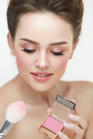 Facial Makeup Beauty Cosmetics. Closeup Of Beautiful Girl With Compact Blush And Cosmetic Brush Applying Make-Up Product On Face. Female With Fresh Skin And Natural Pink Makeup. High Resolution