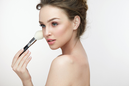 loose skin: Face Makeup Cosmetics. Portrait Of Sexy Young Woman With Clean Skin And Fresh Makeup. Closeup Beautiful Girl Holding Cosmetic Brush And Applying Blush On Facial Skin. Beauty Concept. High Resolution