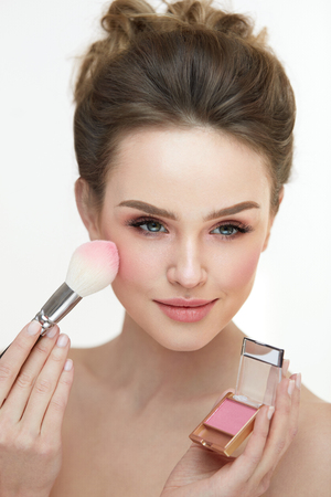 loose skin: Woman Face Makeup. Portrait Of Female Getting Natural Fresh Facial Make-Up. Closeup Beautician Hands With Compact Blush And Brush Applying Blusher On Sexy Girl Face. Beauty Cosmetics. High Resolution