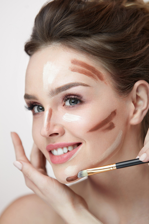 Woman Face Makeup. Closeup Of Hands Applying Contouring And Highlighting Lines On Female Facial Skin. Portrait Of Beautiful Girl With Natural Makeup Using Make-Up Contour Product. High Resolution
