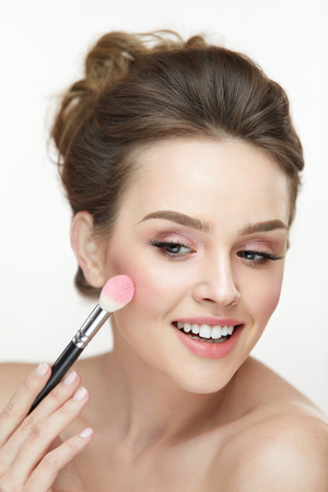 loose hair: Woman Beauty Make-Up. Closeup Of Smiling Girl Applying Blush On Smooth Soft Skin. Portrait Of Beautiful Happy Female With Fresh Makeup Posing On White Background. Facial Cosmetics. High Resolution