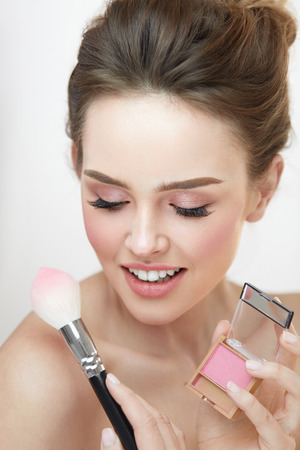 loose hair: Facial Makeup Beauty Cosmetics. Closeup Of Beautiful Girl With Compact Blush And Cosmetic Brush Applying Make-Up Product On Face. Female With Fresh Skin And Natural Pink Makeup. High Resolution