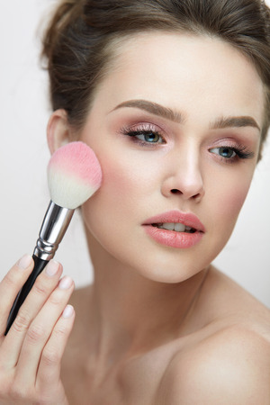Facial Beauty Cosmetics. Portrait Of Attractive Female With Pure Soft Skin Applying Pink Loose Blush On Face. Closeup Of Beautiful Sexy Woman With Fresh Makeup Holding Cosmetic Brush. High Resolution