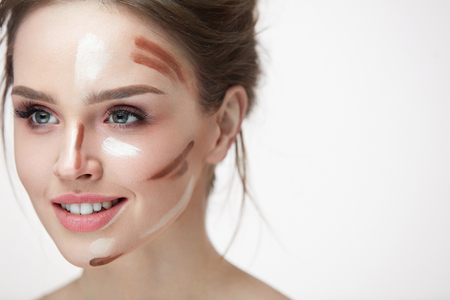 Woman Beauty Makeup. Closeup Of Smiling Young Female Model With Contouring And Highlighting Face Lines On Skin. Portrait Of Beautiful Smiling Girl With Cosmetic Makeup Product On Skin. High Resolution Banco de Imagens