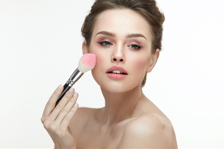 Woman Face Beauty. Closeup Of Sexy Girl Putting Blush With Facial Brush On White Background. Portrait Of Beautiful Young Woman Applying Makeup On Soft Healthy Skin. Cosmetic Concept. High Resolution