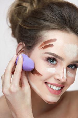 Gezichts make-up en schoonheidsschoonheidsmiddelen. Portret Van Mooie Jonge Vrouw Aanbrengen Contour En Highlight Make-up Lijnen Met Sponge Blender. Close-up Van Sexy Jonge Vrouwelijke Doen Facial Make-up. Hoge resolutie