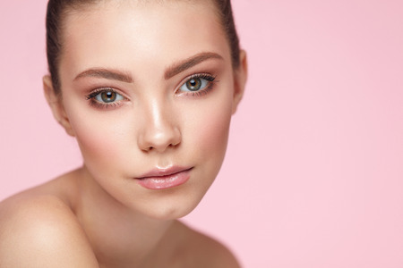 girl  care: Beauty Face Cosmetics. Portrait Of Beautiful Young Woman With Smooth Pure Skin And Fresh Natural Makeup. Closeup Of Attractive Sexy Girl Posing On Pink Background. Skin Care Concept. High Resolution Stock Photo
