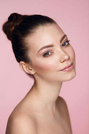 美容女性の顔。柔らかくなめらかな皮膚とプロの天然顔メイクと美しい若い女性モデルのクローズ アップ。ピンクの背景に完璧なメイクとセクシー