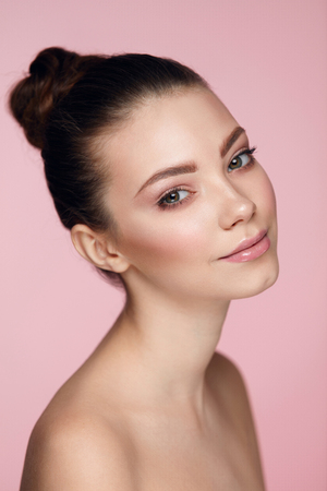 Beauty Woman Face. Closeup Of Beautiful Young Female Model With Soft Smooth Skin And Professional Natural Facial Makeup. Portrait Of Sexy Girl With Perfect Make-up On Pink Background. High Resolution
