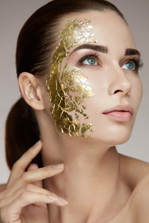 Spa Procedure. Portrait Of Sexy Girl With Gold Mask On Facial Skin Caressing Body. Closeup Of Attractive Woman With Smooth Skin And Cosmetic Product On Face. Beauty Concept. High Resolution Stock fotó