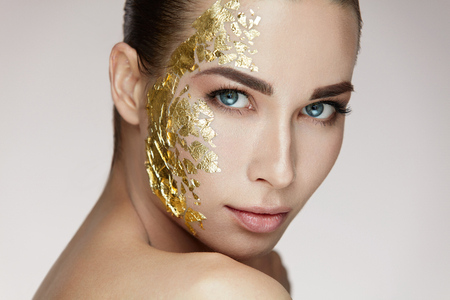 Beauty Woman Face. Closeup Of Beautiful Healthy Girl With Cosmetic Gold Mask On Soft Smooth Skin. Portrait Of Young Female With Natural Makeup Doing Skin Care Procedure. Cosmetics. High Resolution